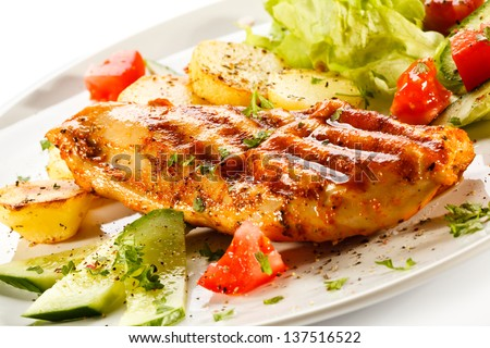 Grilled chicken fillet, baked potatoes and vegetables - stock photo