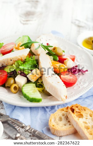 Grilled chicken fillet with fresh vegetable salad on white wooden background, selective focus - stock photo
