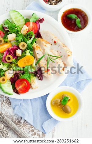 Grilled chicken fillet with fresh vegetable salad on white wooden background, top view - stock photo