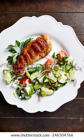 Grilled chicken fillet with salad and fresh herbs - stock photo