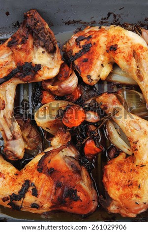 grilled chicken legs with tomatoes and thyme cooked on yellow ceramic pan isolated on white background - stock photo