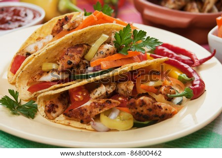 Grilled chicken meat, vegetable and hot chili peppers in taco shells - stock photo