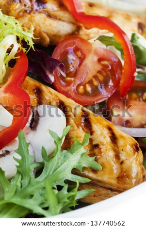 Grilled chicken salad, with lettuce, capsicum, mushrooms, tomatoes and red onion. - stock photo