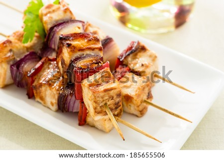 Grilled chicken skewers with vegetables on white plate - stock photo