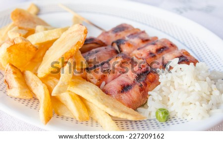Grilled chicken souvlaki rolls with french fried potatoes and boiled rice on a white plate - stock photo