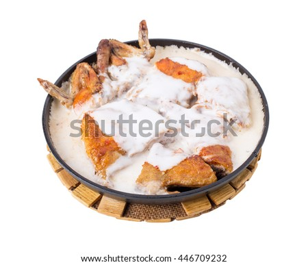 Grilled chicken thighs with sour cream in frying pan. Isolated on a white background. - stock photo
