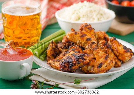Grilled chicken wings with hot and spicy chili sauce, baked bread with seeds, jasmine rice with herbs and beer - stock photo