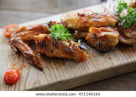 Grilled Chicken Wings with Red Spicy Sauce on wood background - stock photo
