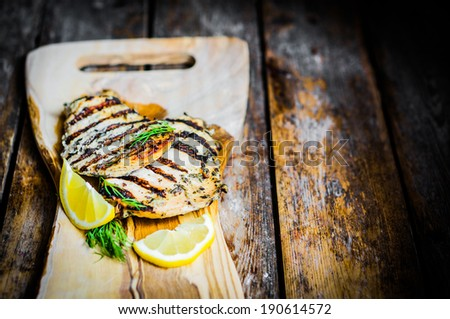 Grilled chicken with herbs and lemon on wooden background - stock photo