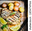 Grilled chicken with potatoes and herbs on wooden background - stock