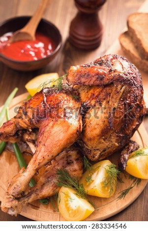 Grilled chicken with sauce and tomatoes on wooden plate
