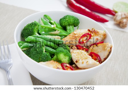 Grilled chilli chicken with steamed broccoli, snow peas, green beans and ginger - stock photo