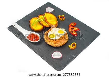 Grilled cutlet, fries, fried egg and vegetables - stock photo