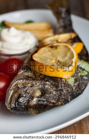 Grilled dorado fish on plate above wooden background