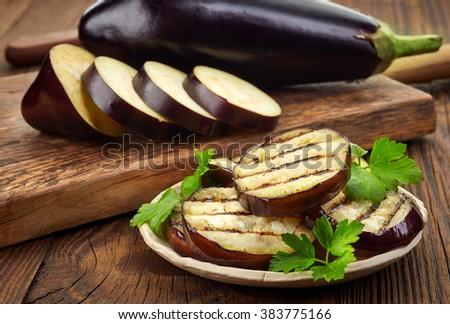 grilled eggplant and parsley leaves on wooden table - stock photo