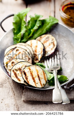 Grilled eggplants in a vintage metal bowl with salad leaves  on a wooden background - stock photo
