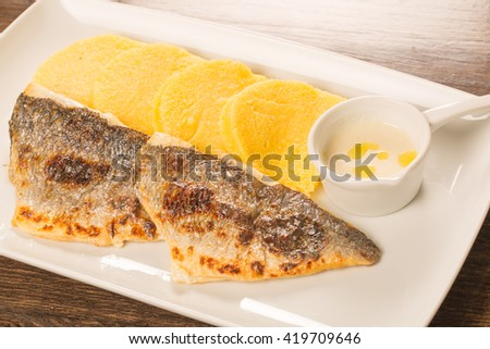 Grilled fish fillet with polenta on a white plate with wooden table - stock photo
