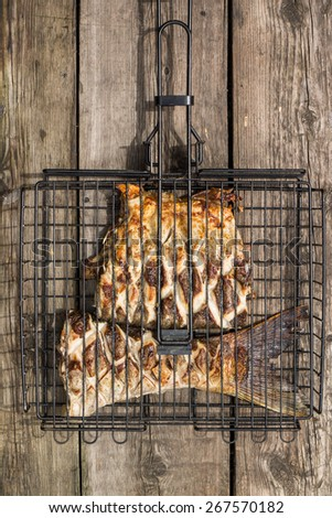 Grilled fish in barbecue on wood background. Outdoor activity eating background - stock photo