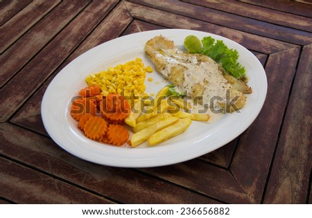 grilled fish steak with vegetables corn and french fries