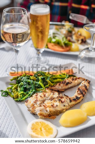 Grilled fish with boiled potatoes and greens as it served in Lisbon, Portugal.