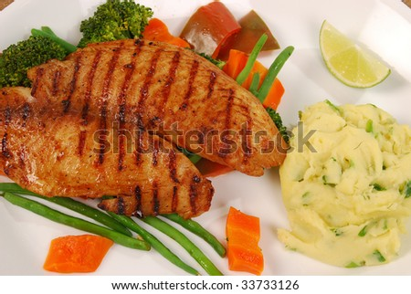 grilled fish with carrots, potatoes pure on white plate on coffee background