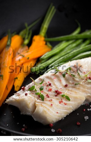 grilled fish with green beans and carrots on frying pan - stock photo