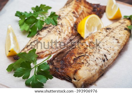 Grilled fish with herbs and lemon on rustic background - stock photo