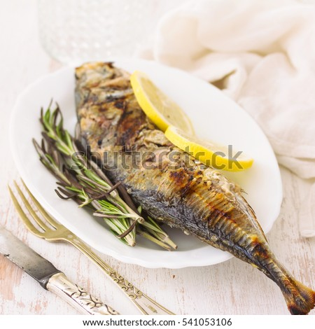 grilled fish with lemon on plate