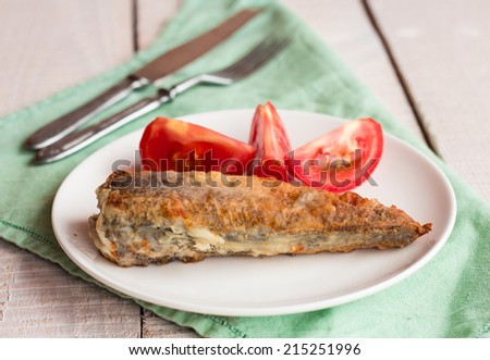 grilled fish with tomato on a plate, fork and knife on a white wooden background - stock photo