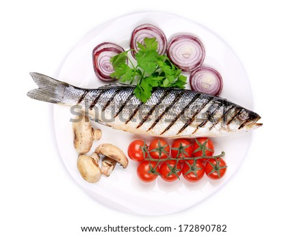 Grilled fish with vegetables. On a white plate. - stock photo