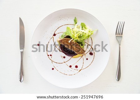 Grilled foie gras with sweet sauce in white dish - selective focus point - stock photo