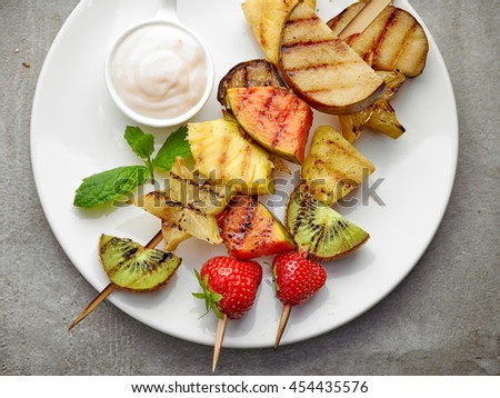 grilled fruits on wooden skewers and yogurt sauce, top view - stock photo