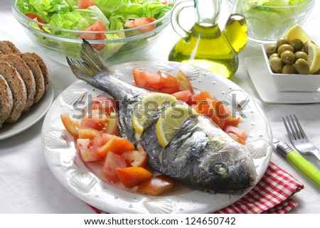grilled gilt head bream with tomato salad olive oil and olives. Healthy mediterranean diet - stock photo