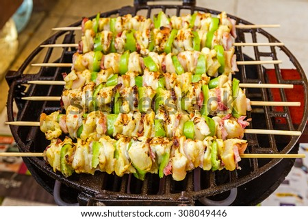Grilled gourmand chicken skewers are made with white meat, bacon and pieces of green paprika being turned on the BBQ. - stock photo