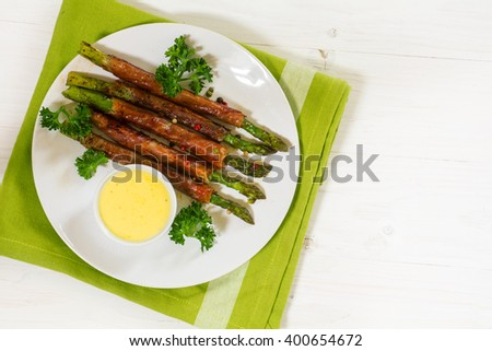 grilled green asparagus wrapped in prosciutto bacon with parsley garnish and hollandaise sauce, plate, green napkin on a white painted wooden background, large copy space, view from above - stock photo