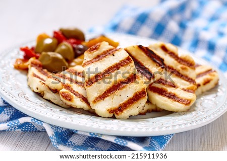 Grilled halloumi cheese with olives and pepers - stock photo