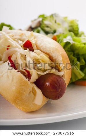 Grilled Hot Dog with sauerkraut and hot red peppers, with side salad - stock photo