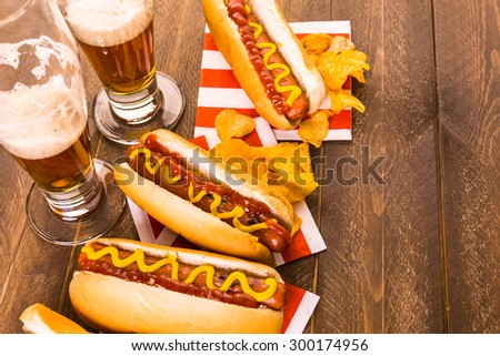 Grilled hot dogs with mustard and ketchup on the table with draft beer. - stock photo