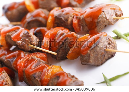 Grilled juicy skewered shashlik on a plate with ketchup.