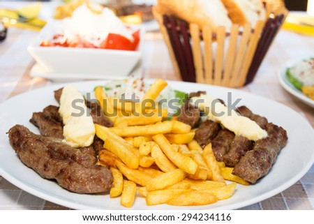 Grilled kebab - barbecued minced meat with french fries served on a table - stock photo
