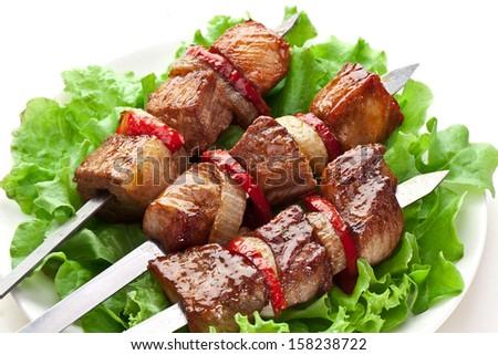 Grilled kebab (shashlik) on spits on the lettuce leaves. - stock photo