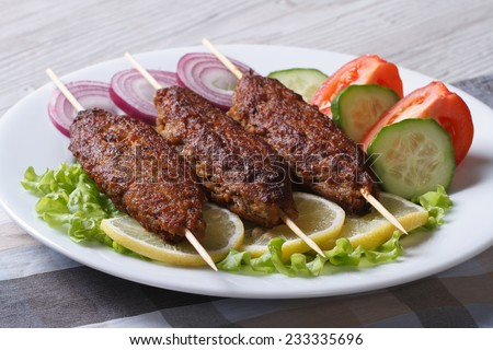 Grilled kebabs on wooden skewers and fresh vegetables on a plate close-up. horizontal  - stock photo