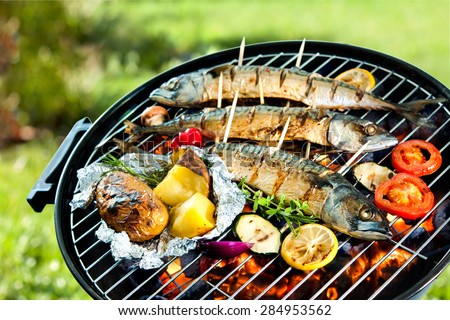 Grilled mackerel fish with baked potatoes over the coals on a barbecue - stock photo