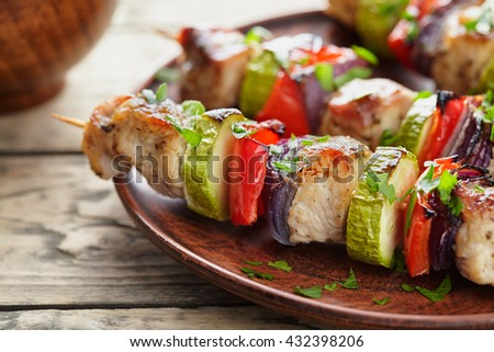 Grilled marinated turkey or chicken meat shish kebab skewers with ketchup sauce, chopped parsley and tomatoes on rustic wooden table background. Traditional barbecue grill food - stock photo