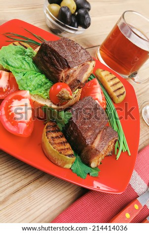 grilled meat : beef ( lamb ) garnished with vegetables , juice and olives on red plate over wooden table