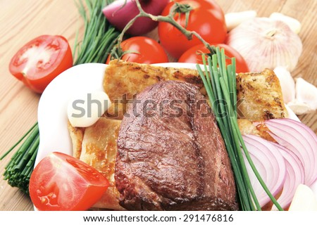 grilled meat : beef ( pork ) garnished with tomatoes salad in bowl , green chives , and tomatoes on side on wooden table