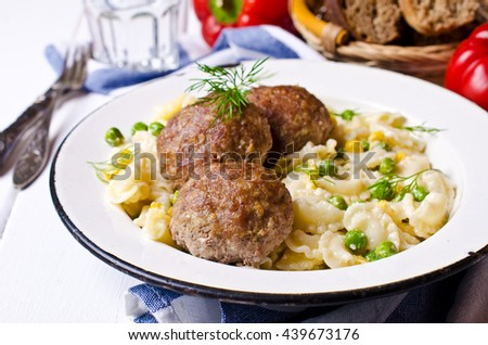 Grilled meat cutlets with pasta and vegetables on a wooden background. Selective focus.