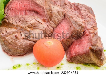 Grilled meat on a platter vegetables- greens, tomato, orange, spinach - stock photo