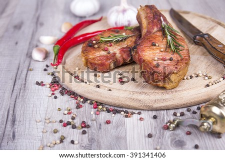 Grilled meat (pork) steaks on cutting board with hot peppers, garlic and knife, peppers mix, and rosemary on wooden cutting board  - stock photo