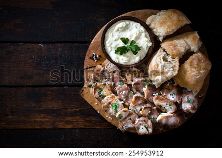 Grilled meat slices and cream cheese with bread on wooden background with blank space  - stock photo